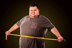 Man belly fat with tape measure weight loss around body . Man belly fat with tape measure weight loss around body on black background. Person is happy that he Royalty Free Stock Photo