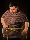 Man belly fat with tape measure weight loss around body . Man belly fat with tape measure weight loss around body on black background. First day of diet. Person Royalty Free Stock Photo
