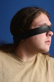 Man with a belt over his eyes Royalty Free Stock Photo