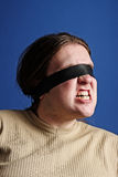 Man with a belt over his eyes Stock Images
