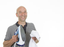Man with bemused expression holding an iron Stock Photography