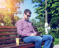 A man on a bench in a city park, read a message on the tablet, watching a movie or TV show, next to a glass of coffee or Stock Photo