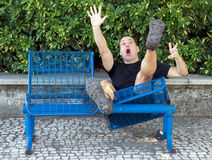Man on a bench falling down Stock Image