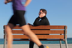 Man on a bench having a phone call while a runner is passing by Royalty Free Stock Photography