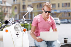Man on bench with laptop near scooter Stock Photo