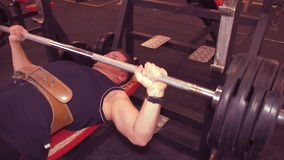 Man bench press. Man lying barbell presses in the gym, on the bench. The guy has been in the gym. stock video footage