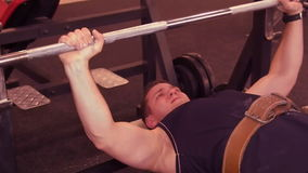 Man bench press. Man lying barbell presses in the gym, on the bench. The guy has been in the gym. stock footage