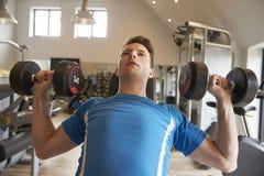Man bench pressing dumbbells at a gym, close up Royalty Free Stock Photo