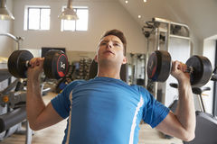 Man bench pressing dumbbells at a gym, close up Royalty Free Stock Image