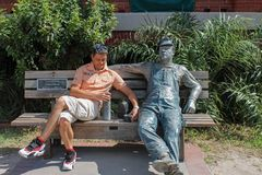 Man on a bench with the sculpture `Lunchbreak` by J. Seward Johnson on Key West. Museum of Art and History sculpture exhibit. Key West, Florida, USA - November Royalty Free Stock Photos