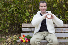 Man on bench shaping heart with his hands Royalty Free Stock Photo