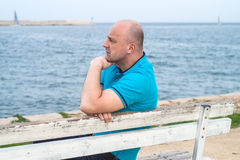Man on bench. A man sitting on the bench and looking at the sea Stock Photos