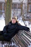 Man on bench in winter Stock Images