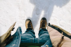 Man bend down the head looking for his boots standing on snow. First-person view. Man bend down the head looking for his boots standing on snow stock images