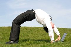 Man bending backwards. Businessman bending over backwards and using laptop Royalty Free Stock Photo