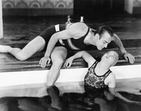 Man bending over to kiss a woman in a swimming pool Royalty Free Stock Images