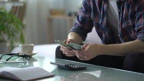 Man beräknande inkomst och kostnader som uppskjuter pengar för att resa, helger lager videofilmer