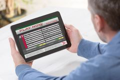 Man betting on sports. Over shoulder view on tablet with scores Royalty Free Stock Photos