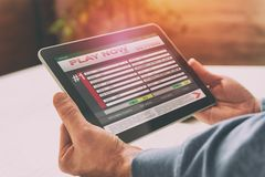 Man betting on sports. Over shoulder view on tablet with scores Stock Photography