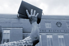 Man with bible at protest. Man holding up bible in front of court house Stock Photos