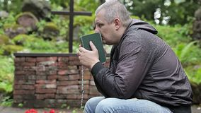 Man with Bible and rosary praying at outdoors church near cross stock video footage