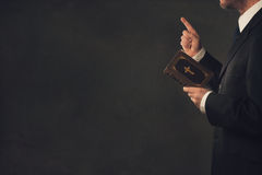 Man with a Bible and a wagging finger. A standing man in Suit with a Bible and a wagging finger stock image