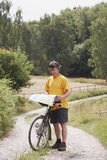 Man with bicycle. Stopping on rural road and looking at map Royalty Free Stock Images