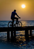 Man on bicycle. Silhouette of a man riding a bicycle on a bridge at sunset Stock Photography