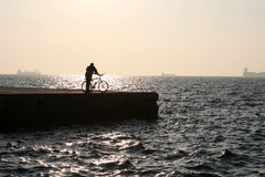 Man with bicycle. A man's sillouette with a bicycle by the sea at sunset Stock Image