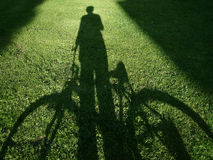Man with bicycle. Shadow of man with the bicycle on the green grass royalty free stock photos