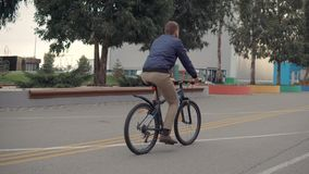 Man on a bicycle alone. Shot from behind of a guy riding a bike alone. Man spending time riding a bicycle, urban man stock video footage