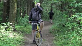 Man on bicycle with cell phone in the park stock video