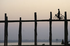 Man with  bicycle crossing the U Bein bridge. Royalty Free Stock Photo