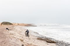 Man on a bicycle, dog and an angler at Swakopmund Royalty Free Stock Photos