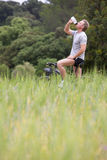 Man on bicycle drinking from water bottle in rural field Royalty Free Stock Images