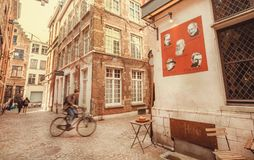 Man on bicycle driving past old style narrow street with restaurant of historical city Royalty Free Stock Images