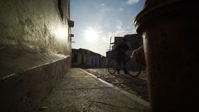 Man with a bicycle going across the empty street at sunset stock video footage