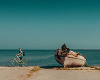 Man on the bicycle. Happy man on a bike near a boat on the Baltic sea Royalty Free Stock Image
