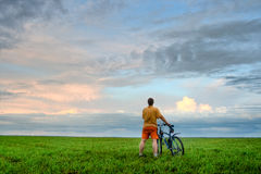 Man with bicycle looking at skies Stock Photos