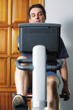 Man on bicycle machine Stock Image