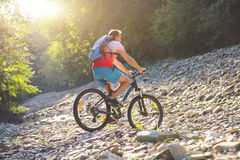 Man on the bicycle by mountain river. Young man with backpack on the bicycle by mountain river Stock Photos