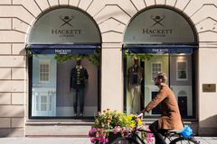 Man in bicycle passing by Hackett London shop royalty free stock images