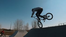 A man on a bicycle performing tricks in the skatepark. Racing and holding a balance on a front wheel stock video