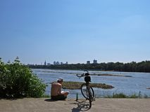 Man with Bicycle Reading and Enjoying View at Panorama of Modern City royalty free stock photography