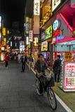 Man on bicycle in Shinjuku Street.  Nighttime scene. Man rides bicycle down Shinjuku street in Tokyo Japan Royalty Free Stock Images