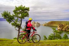 man on a bicycle on the shore of Baikal royalty free stock image