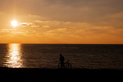 Man and bicycle silhouette at sunset sea Stock Photography
