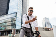 Man with bicycle and smartphone on city street Stock Image