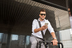 Man with bicycle and smartphone on city street Royalty Free Stock Images