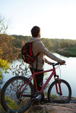Man with a bicycle stands near the river Royalty Free Stock Images